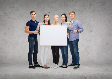 education, advertisement, sale and people concept - group of smiling students pointing at blank white board photo