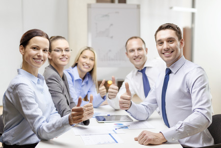 business, success, technology and office concept - smiling business team with tablet pc computer and papers showing thumbs up in office photo