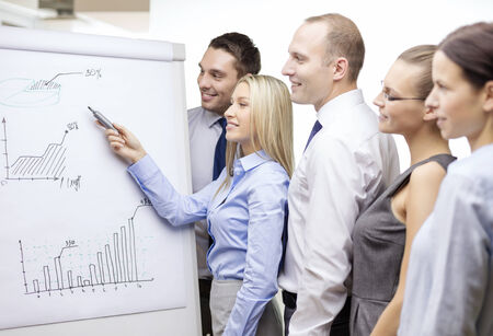 business and office concept - smiling business team with charts on flip board having discussion Stock Photo - 29037394