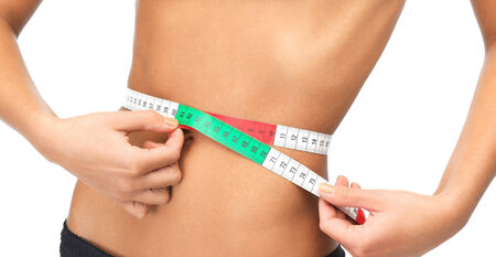 lingerie model: health, dieting and fitness concept - close up of woman measuring her waist with measuring tape