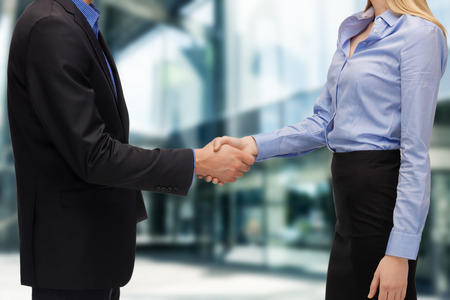 doing business: business and office concept - businessman and businesswoman shaking hands outdoors