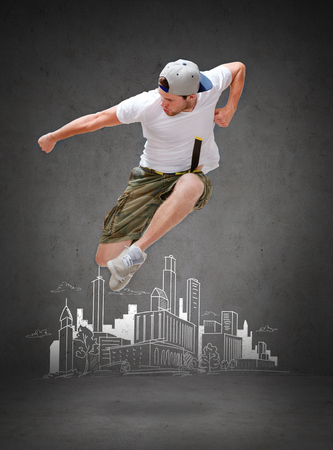 urban dance: dancing, happiness and people concept - male dancer jumping in the air with city drawing in the back Stock Photo