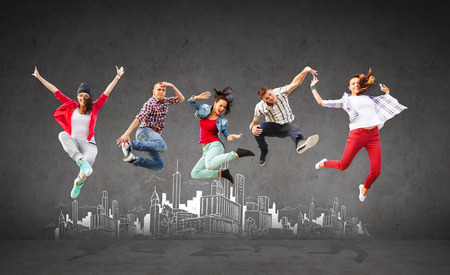 summer, sport, dancing and teenage lifestyle concept - group of teenagers jumping with city drawing in the back photo