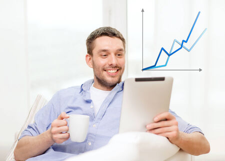 technology, home and lifestyle concept - smiling man working with tablet pc computer and coffee cup at home photo