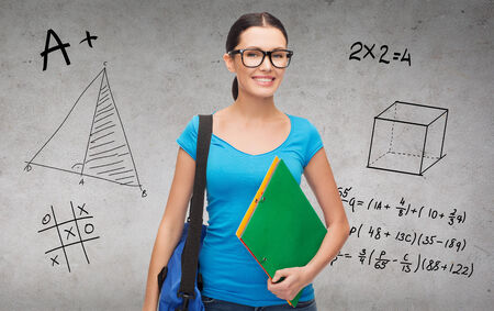 education and people concept - smiling student in eyeglasses with bag and folders standing photo