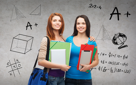 education, technology and people concept - two smiling students with bag, folders and tablet pc standing photo