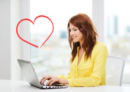 jornada de trabajo: negocios, la educación y la tecnología concepto - estudiante sonriente con el ordenador portátil en el libro de la escuela