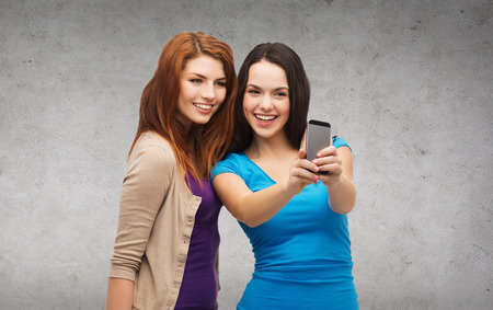 cute girlfriends: technology, friendship and people concept - two smiling teenagers taking picture with smartphone camera