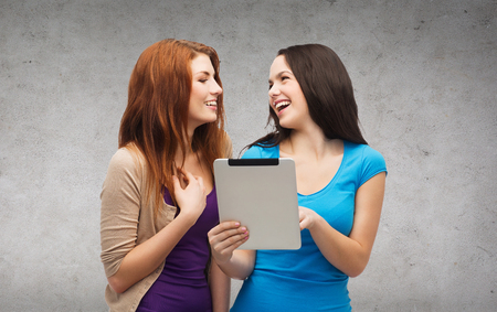 technology, friendship and people concept - two smiling teenagers pointing finger at tablet pc screen and looking at each other photo