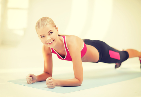 beautiful sporty woman doing exercise on the floor photo
