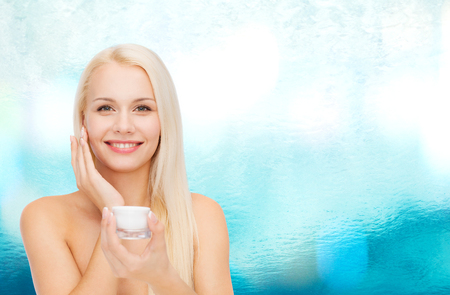 cosmetics, health and beauty concept - beautiful woman applying cream on her skin photo