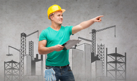 repair, construction and maintenance concept - smiling man in helmet with construction site on back holding clipboard and pointing finger photo