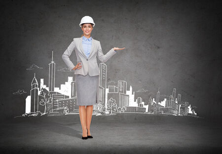 building, developing, advertising and architecture concept - friendly young smiling businesswoman in white helmet holding something on palm photo