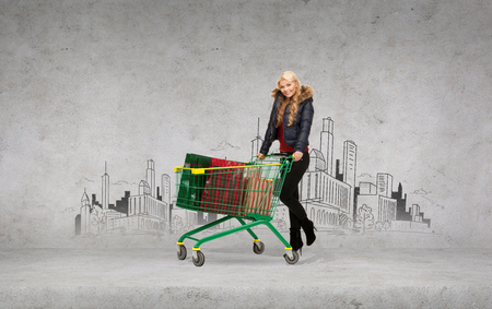shopping, x-mas and winter concept - smiling woman in winter clothes with shopping cart and many bags in it photo