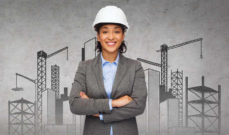 building, developing, construction and architecture concept - smiling businesswoman in white helmet with crossed arms photo