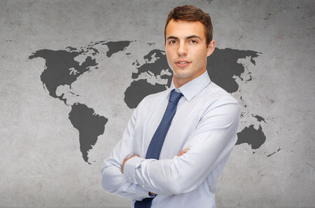 business and office, people concept - friendly young businessman with crossed arms photo