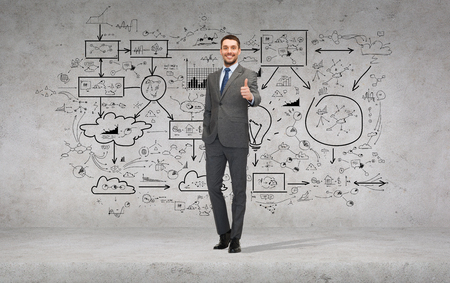 business, gesture and office concept - handsome businessman showing thumbs up with big plan on the back photo