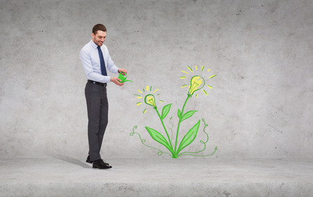 business, ecology and office concept - handsome businessman with green watering can showering flower with light bulbs photo