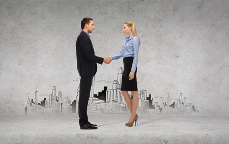 business and office concept - businessman and businesswoman shaking hands with city drawing in the back photo