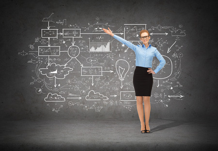 business, advertising and office concept - smiling businesswoman in eyeglasses pointing her hand at big plan photo