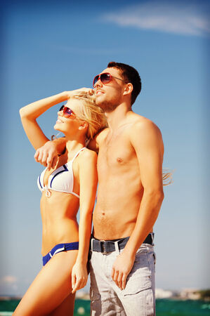 picture of happy couple in sunglasses on the beach, focus on man photo