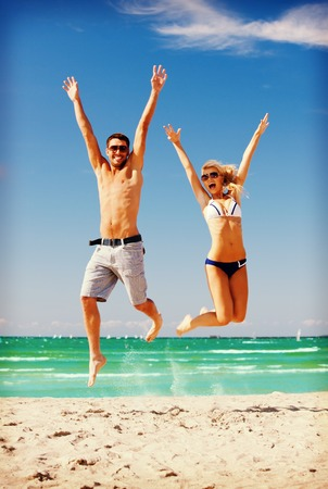 fit man: picture of happy couple jumping on the beach