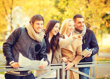 touristic: holidays and tourism concept - group of friends or couples with tourist map in autumn park