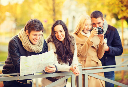 holidays and tourism concept - group of friends or couples with tourist map and camera in autumn park photo