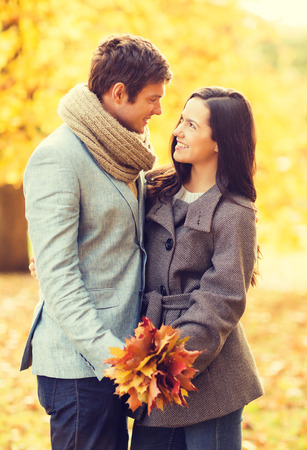 holidays, love, travel, tourism, relationship and dating concept - romantic couple kissing in the autumn park photo