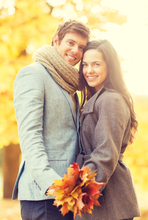 holidays, love, travel, tourism, relationship and dating concept - romantic couple in the autumn park photo