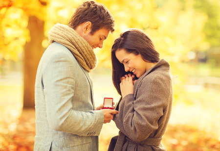 groom: holidays, love, couple, relationship and dating concept - romantic man proposing to a woman in the autumn park