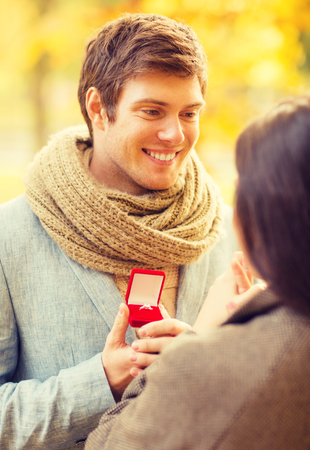 romantic man: holidays, love, couple, relationship and dating concept - romantic man proposing to a woman in the autumn park