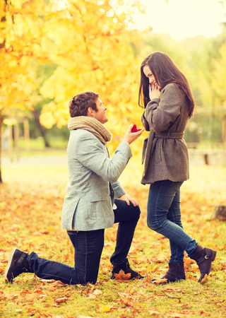girl with rings: holidays, love, couple, relationship and dating concept - kneeled man proposing to a woman in the autumn park