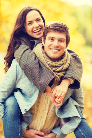 holidays, love, travel, tourism, relationship and dating concept - romantic couple playing in the autumn park photo