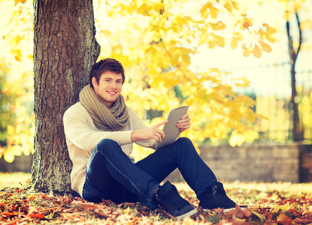business, communication, modern technology and leisure concept - man with tablet pc in autumn park photo