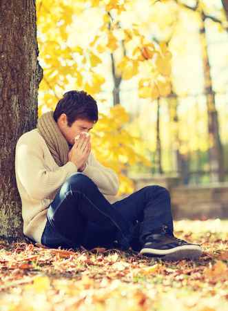 grippe: healthcare and medicine concept - ill man with paper tissue in autumn park
