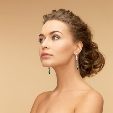 beauty and jewelry concept - beautiful woman in diamond and emerald earrings