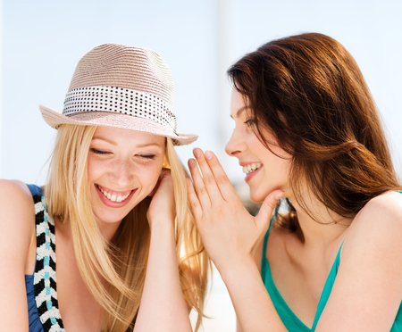 friendship, happiness and people concept - two smiling girls whispering gossip photo