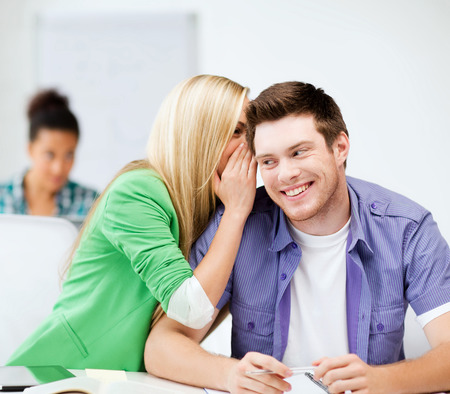 education concept - male and female students talking at school or college photo
