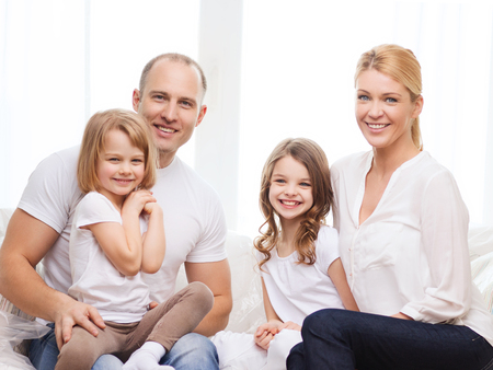 family, children and home concept - smiling parents and two little girls at home photo