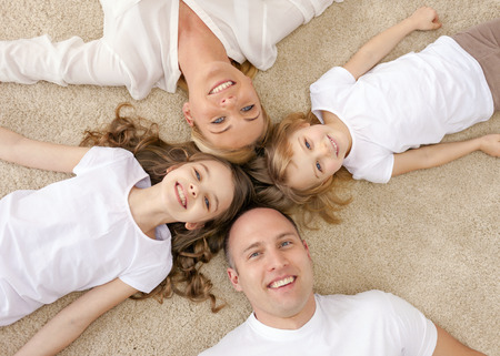 family, children and home concept - smiling family with and two little girls lying in circle on floor at home photo