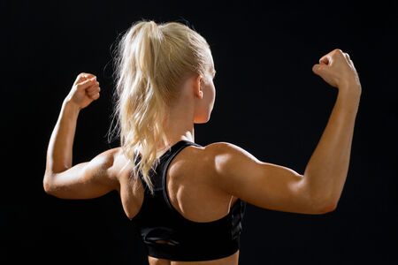 woman black background: fitness, sport and diet concept - sporty woman form the back flexing her biceps Stock Photo