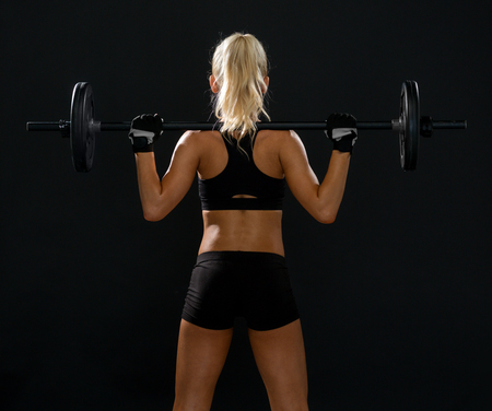 woman black background: fitness, sport and dieting concept - sporty woman exercising with barbell from back Stock Photo
