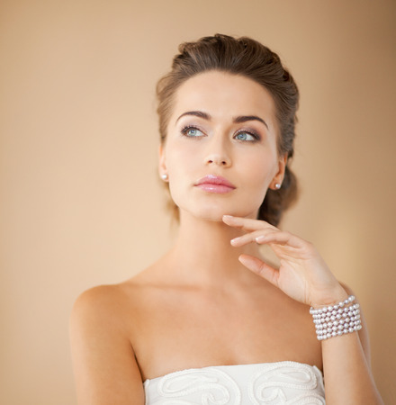 beautiful bride wearing pearl earrings and bracelet photo