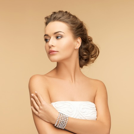 a bracelet: beauty and jewelery concept - beautiful woman with pearl earrings and bracelet