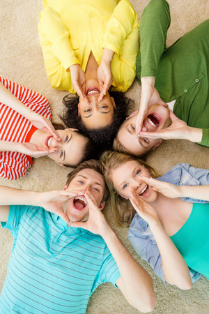 education and happiness concept - group of young smiling people lying down on floor in circle screaming and shouting photo