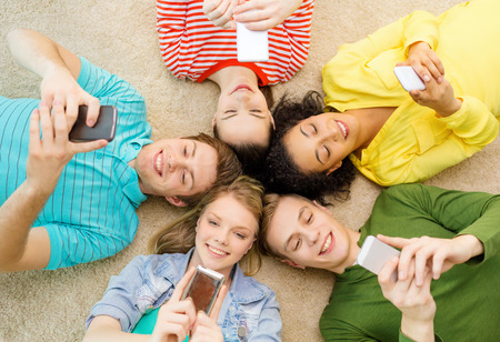 lying down on floor: education, technology and happiness concept - group of young smiling people lying down on floor in circle with smartphones