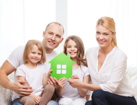 eco house: real estate, family, children and home concept - smiling parents and two little girls holding green house