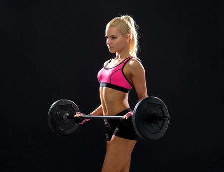fitness, sport and dieting concept - sporty woman exercising with barbell photo