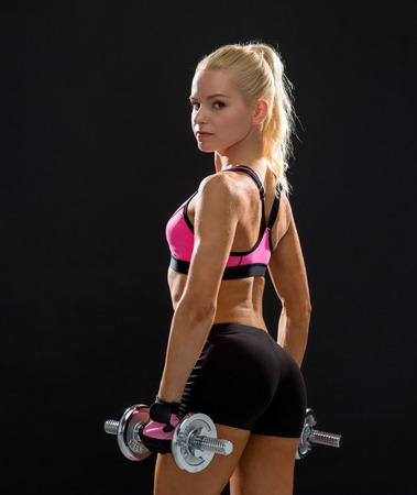 fitness, exercising and dieting concept - sporty woman with heavy steel dumbbells from back photo